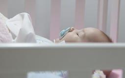 Bebê de sono de quatro meses que encontra-se no berço com chupeta fotos de stock