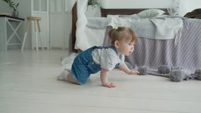 Bebê de sorriso adorável que rasteja no assoalho para a câmera