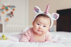Bebê de sorriso asiático adorável bonito da raça misturada quatro meses de encontro velho na barriga na cama imagem de stock