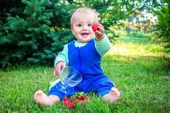 Bebê de sorriso bonito que senta-se em uma grama verde fresca em um parque e que dá a morango ao visor Foto de Stock