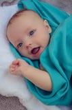 Bebê de sorriso coberto na cobertura azul fotografia de stock royalty free