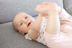 Bebê de sorriso com os olhos azuis que jogam no sofá Foto de Stock Royalty Free