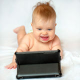 Bebê de sorriso com PC da tabuleta em casa Foto de Stock Royalty Free