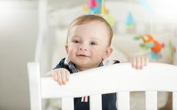 Bebê de sorriso do bebê de nove meses que está na ucha de madeira branca Imagens de Stock Royalty Free