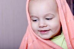 Bebê de sorriso envolvido em uma toalha cor-de-rosa Fotografia de Stock