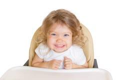 Bebê de sorriso feliz na cadeira alta Isolado no branco Fotografia de Stock