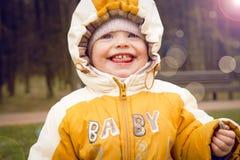Bebê de sorriso na natureza na roupa morna na mola adiantada Criança alegre na capa fora Retrato da criança com sorriso feliz Imagens de Stock Royalty Free