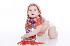 Bebê de sorriso no chapéu e no lenço feitos malha Fotografia de Stock