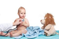 Bebê de sorriso pequeno dos exames do doutor das crianças Imagens de Stock