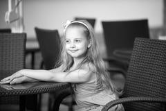 Bebê de sorriso pequeno no vestido azul perto da tabela do café Imagens de Stock Royalty Free