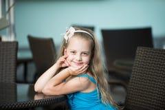 Bebê de sorriso pequeno no vestido azul perto da tabela do café Foto de Stock