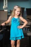 Bebê de sorriso pequeno no vestido azul perto da tabela do café Foto de Stock Royalty Free