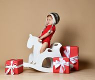 Bebê de sorriso pequeno que senta-se em um cavalo branco, balanço de madeira fotografia de stock