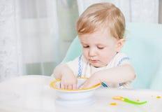 Bebê de sorriso que come o alimento na cozinha Imagens de Stock Royalty Free