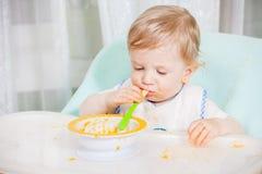 Bebê de sorriso que come o alimento na cozinha Imagem de Stock Royalty Free