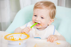 Bebê de sorriso que come o alimento na cozinha Fotos de Stock Royalty Free