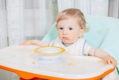 Bebê de sorriso que come o alimento na cozinha Fotografia de Stock Royalty Free