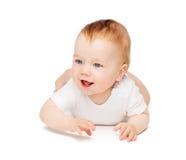 Bebê de sorriso que encontra-se no assoalho fotografia de stock royalty free