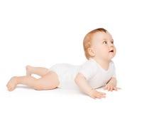 Bebê de sorriso que encontra-se no assoalho e que olha acima foto de stock