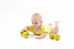 Bebê de sorriso que encontra-se no fundo para incluir maçãs foto de stock