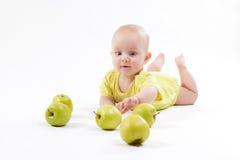 Bebê de sorriso que encontra-se no fundo para incluir maçãs imagem de stock