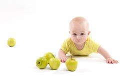 Bebê de sorriso que encontra-se no fundo para incluir maçãs fotografia de stock royalty free