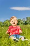 Bebê de sorriso que senta-se na grama verde apenas Foto de Stock Royalty Free
