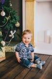 Bebê de sorriso que senta-se sob a árvore de Chritmas perto da chaminé Fotografia de Stock Royalty Free