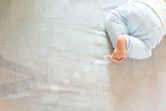 Bebê descalço na cama Fotos de Stock Royalty Free