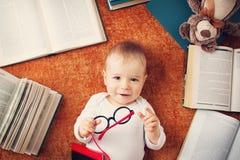 Bebê do bebê de um ano com spectackles e uma peluche fotografia de stock royalty free