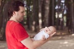 Bebê do bebê de um mês que encontra-se no braço do seu pai imagem de stock royalty free