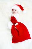 Bebê do Natal que desgasta o saco vermelho da terra arrendada do chapéu imagem de stock