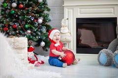 Bebê do rapaz pequeno que guarda um brinquedo grande da árvore de Natal Imagens de Stock Royalty Free