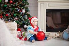 Bebê do rapaz pequeno que guarda um brinquedo grande da árvore de Natal Foto de Stock