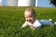 Bebê do sorriso na grama Fotografia de Stock Royalty Free