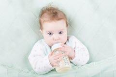 Bebê doce com leite bebendo dos olhos azuis grandes Fotografia de Stock