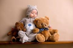 Bebê doce no urso total, dormindo em uma prateleira com peluche b foto de stock