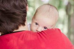 Bebê doce que encontra-se no ombro do pai fotografia de stock