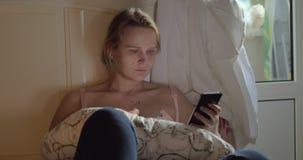 Bebê dos cuidados da mulher e Internet surfando no móbil filme