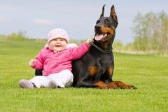 Bebê e cão preto grande Fotos de Stock Royalty Free