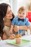 Bebê e mãe com o bolo de aniversário na tabela foto de stock royalty free