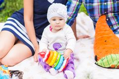 Bebê e mãe e pai que jogam na grama verde, close-up do piquenique da família imagem de stock royalty free