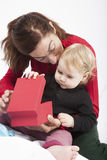 Bebê e mamã que abrem a caixa vermelha Fotografia de Stock Royalty Free