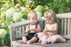 Bebê e menina no vestido formal que senta-se no banco de madeira em um jardim bonito Fotos de Stock Royalty Free
