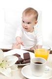 Bebê e uma bandeja com pequeno almoço Foto de Stock