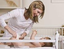 Bebê em mudança da mulher Fotografia de Stock Royalty Free