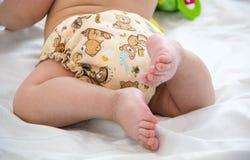 Bebê em pilhas modernas do eco de close-up do foco seletivo dos tecidos de pano e das buchas da substituição no fundo brilhante,  Fotos de Stock