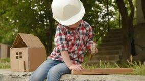Bebê em scoopes de um capacete da construção um prego video estoque