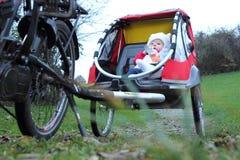 Bebê em um reboque da bicicleta da criança Fotografia de Stock Royalty Free