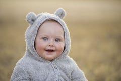 Bebê em um terno do urso no por do sol Fotografia de Stock